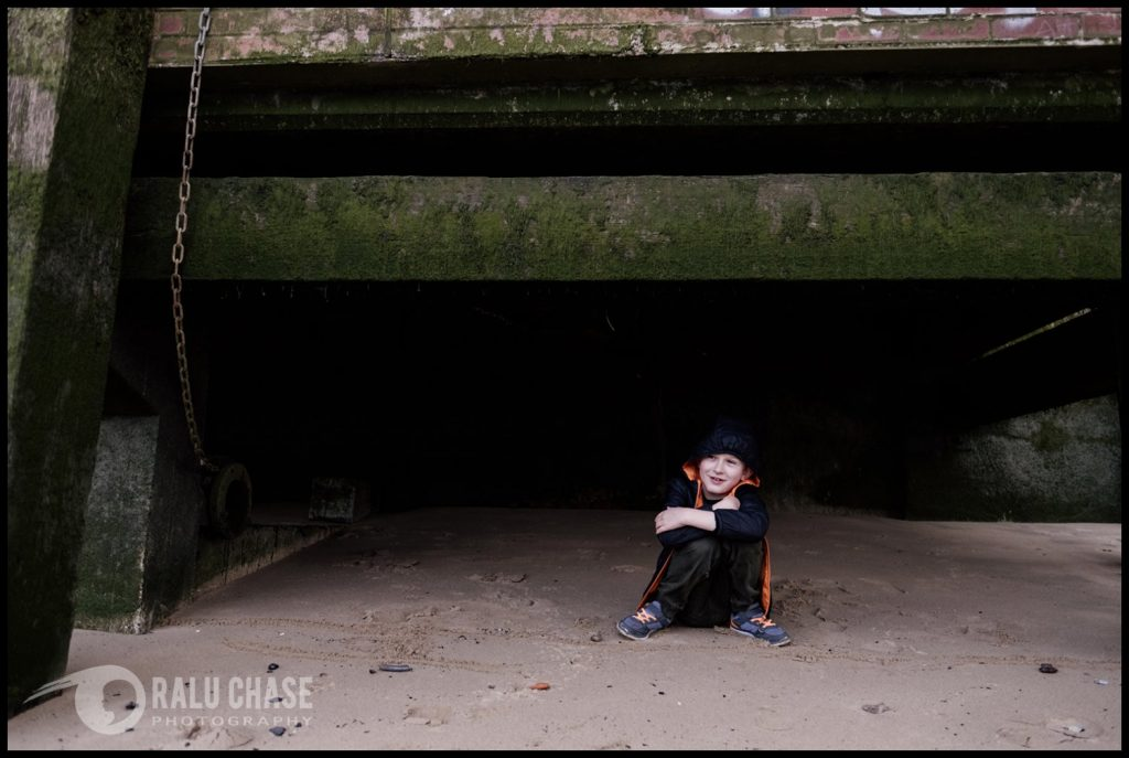 boy hiding under the south bank of the thame's during a London family session