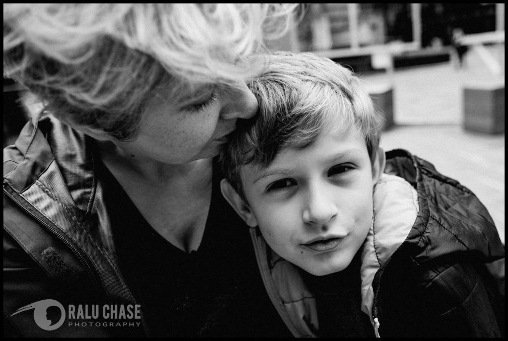 a black and white photo a mom kissing her son and holding him tight. the boy is looking straight at the camera during a London family photo session.