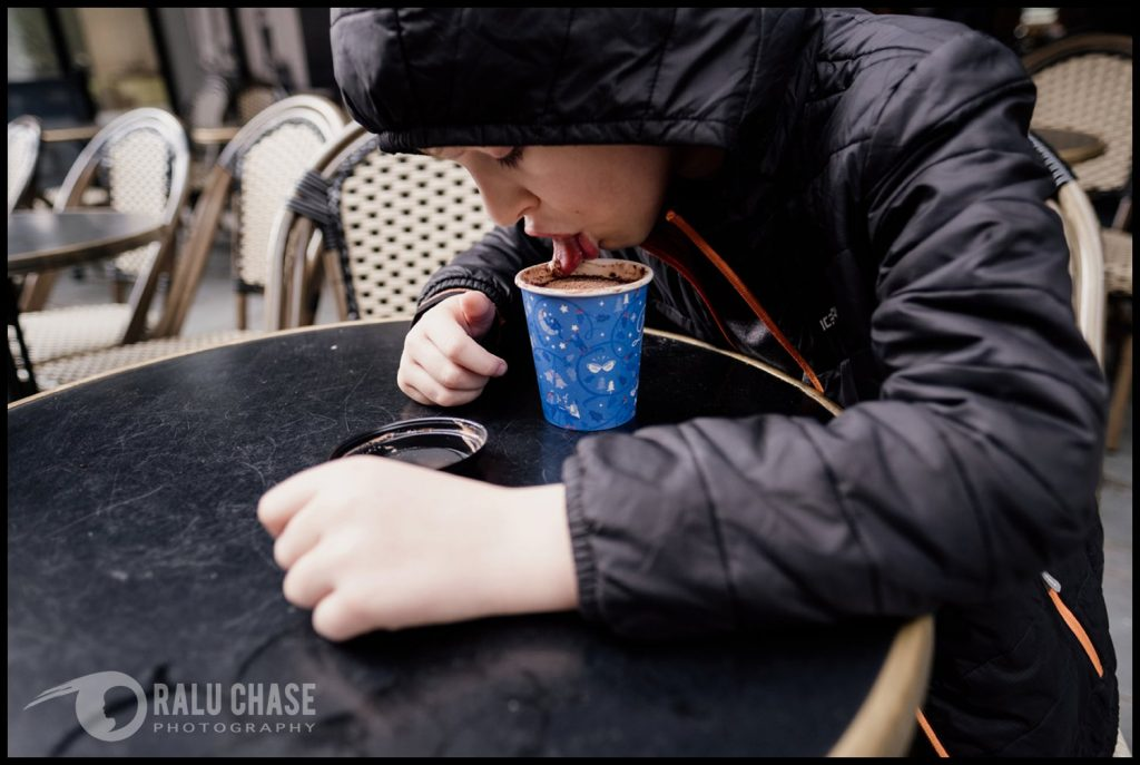 boy licking the foam of the edge of his cafe nero hot chocolate during a London documentary family session. the photograph is taken by Ralu Chase - a London documentary family photographer