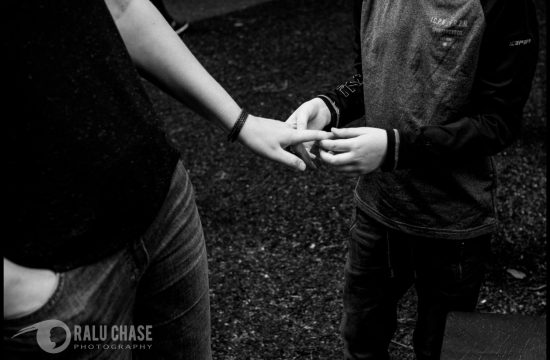 a close up of a boy and his mom holding hands