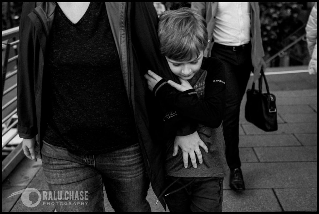 boy holding tight onto his mom's arm while walking in Central London, on golden jubilee bridge, during a family session