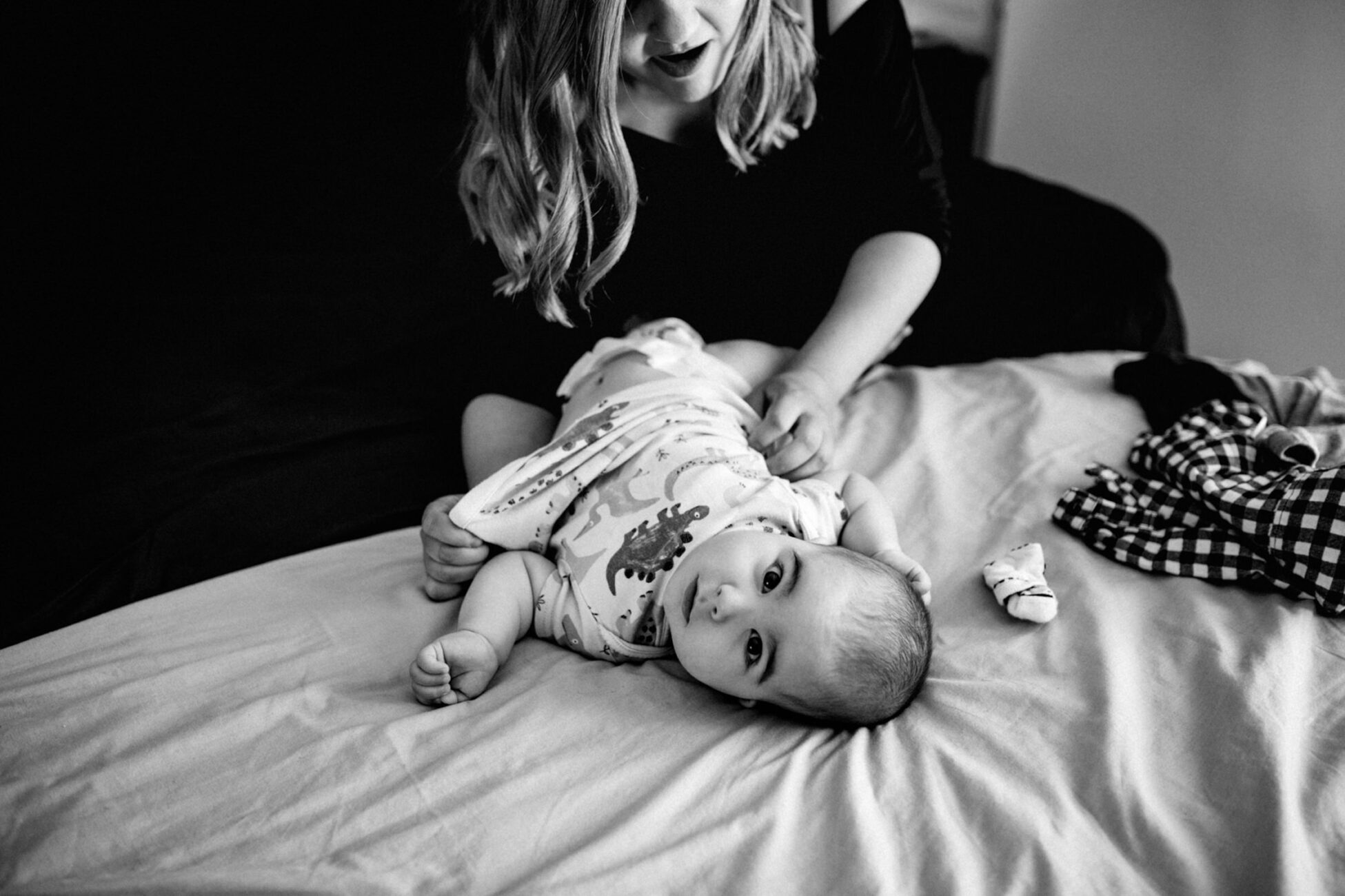 mom changing baby on the bed during a newborn photoshoot in essex