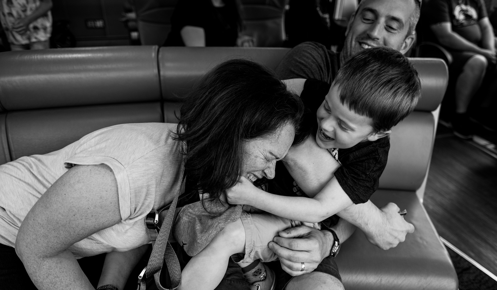 boy pulling mom's head towards him while on aa boat ride on the Thames during a documentary family photoshoot