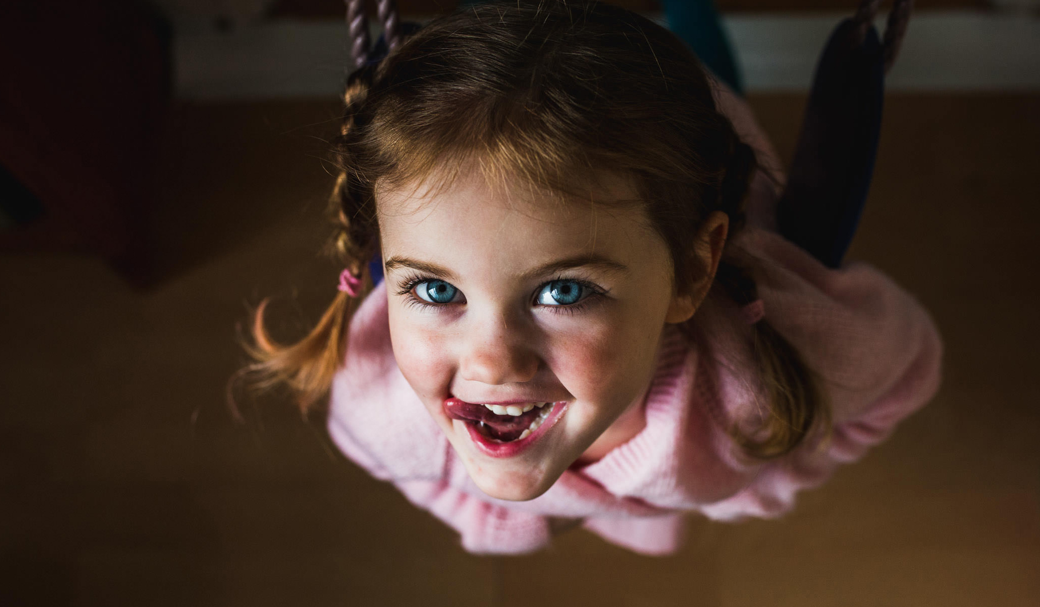 girl looking at camera while swinging on an indoor swing during a documentary family photoshoot in Frinton-on-Sea