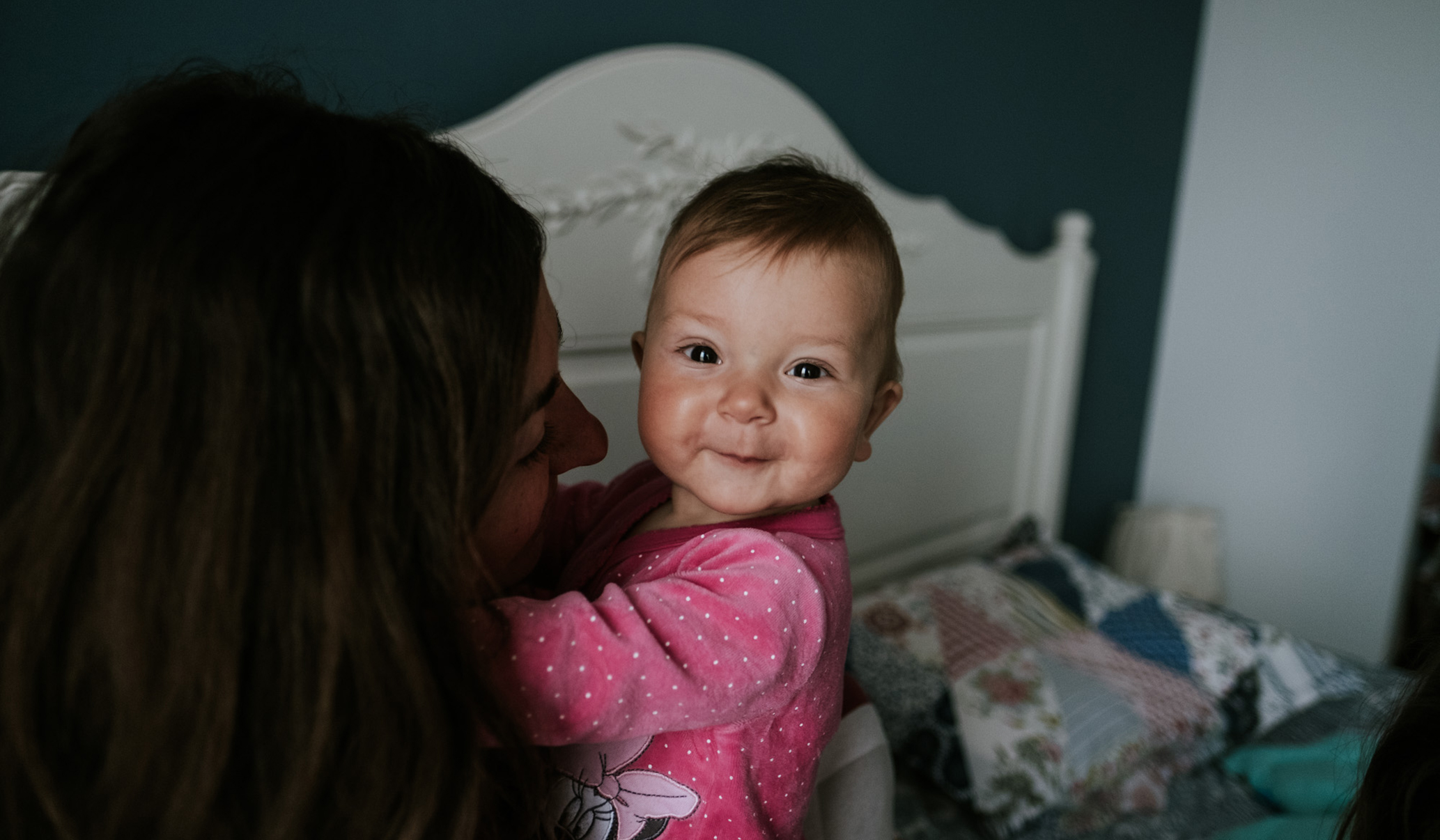 baby girl looking at camera, held by mom during a documentary family photoshoot