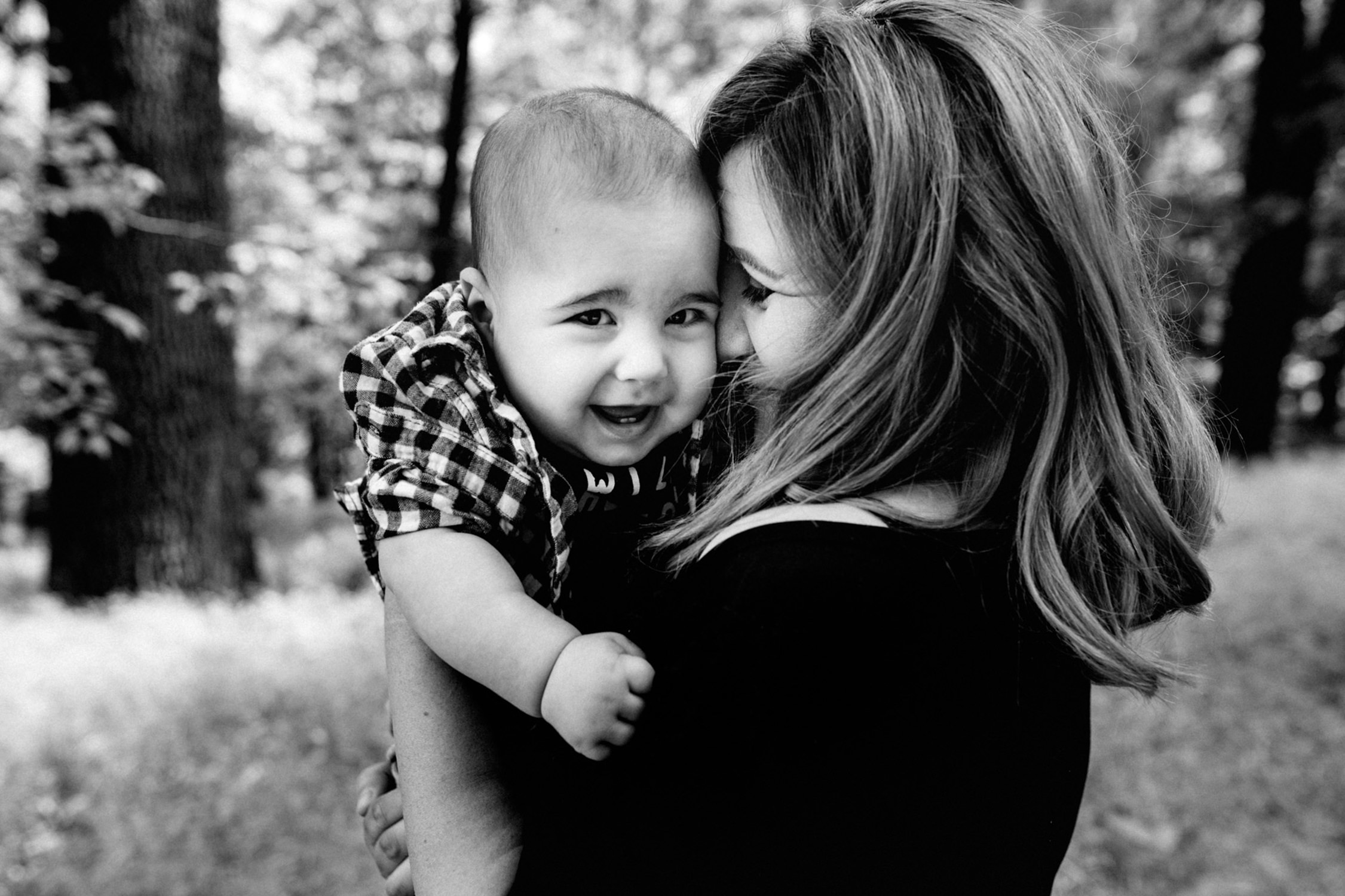 mom and baby boy sharing a cure moment together. the baby boy is smiling and looking at the camera while mom is holding him tight to her face