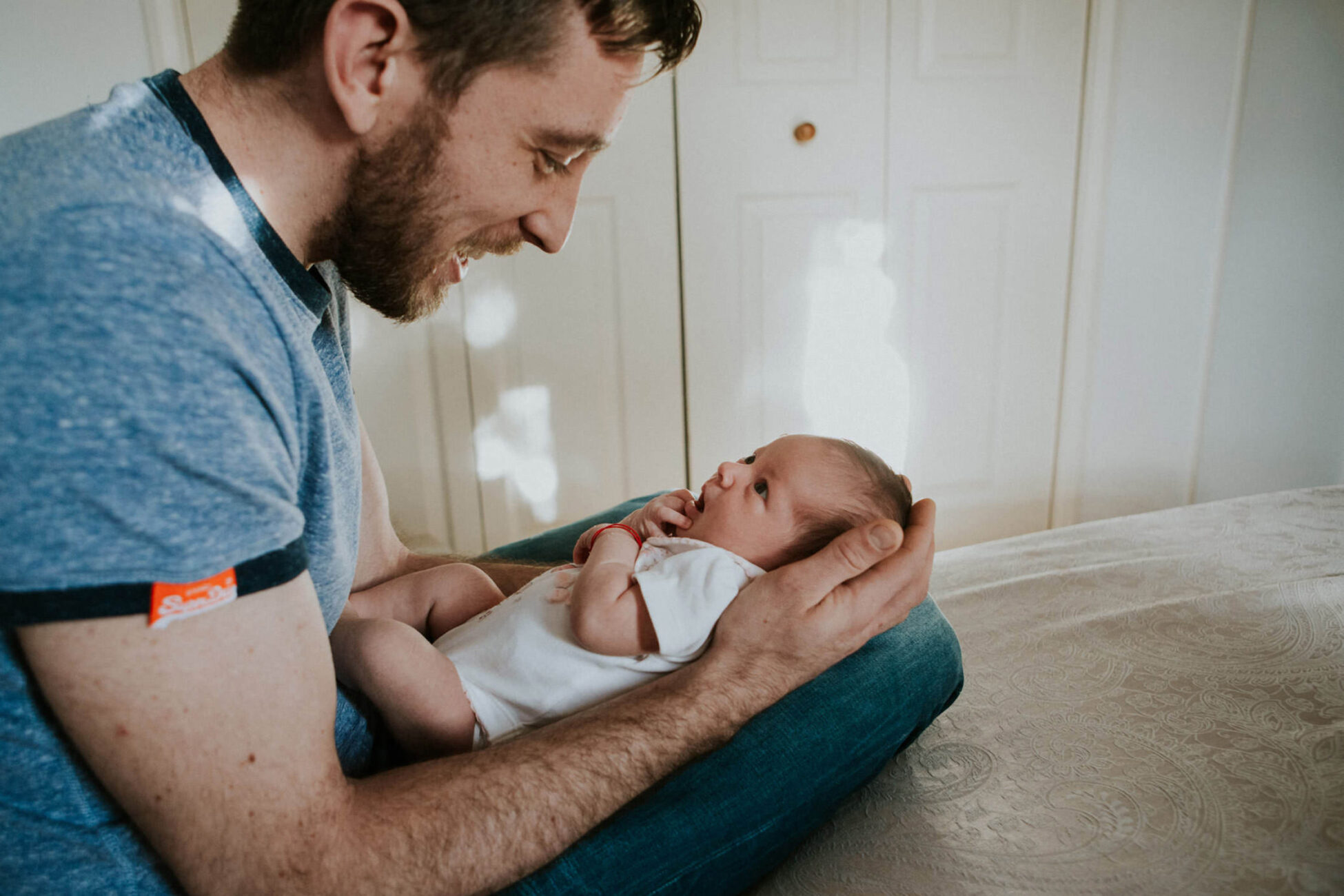 dad talking to his newborn baby girl during a newborn photoshoot