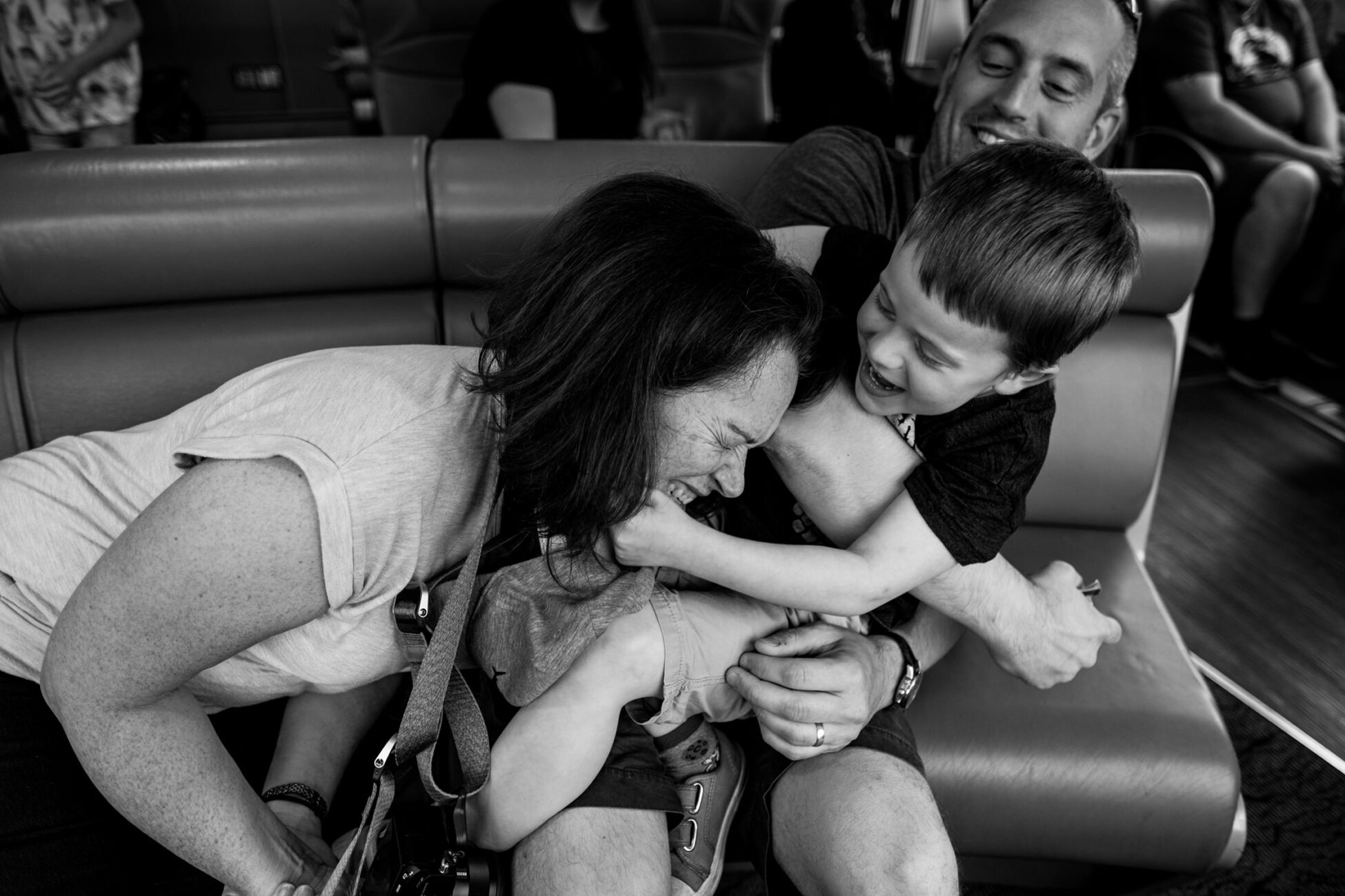 boy pulling hard on his mom's neck family photographer in essex