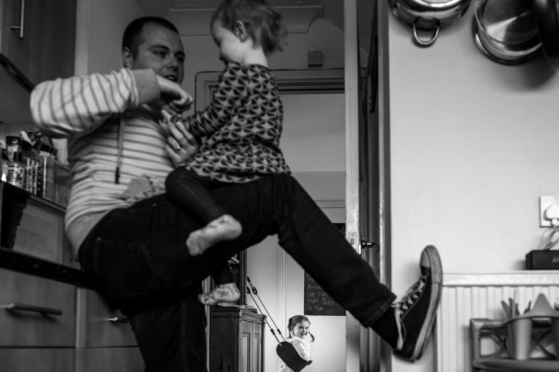 in the foreground dad playing with his little daughter while you can see in the background the other daughter swinging on a indoor swing