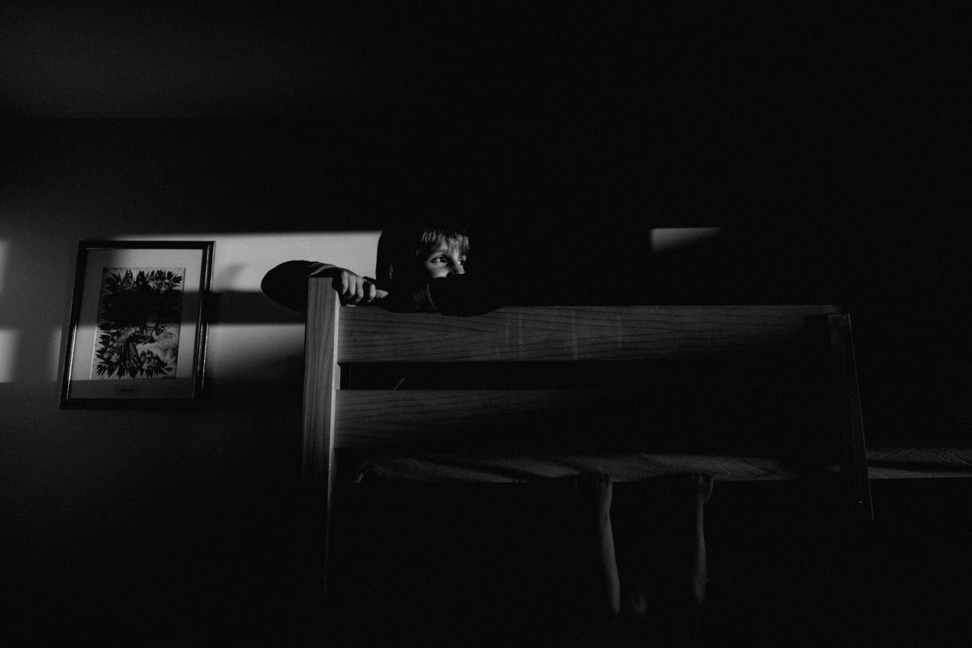 essex family photographer little boy looking out the window while sitting on a top bunk bed
