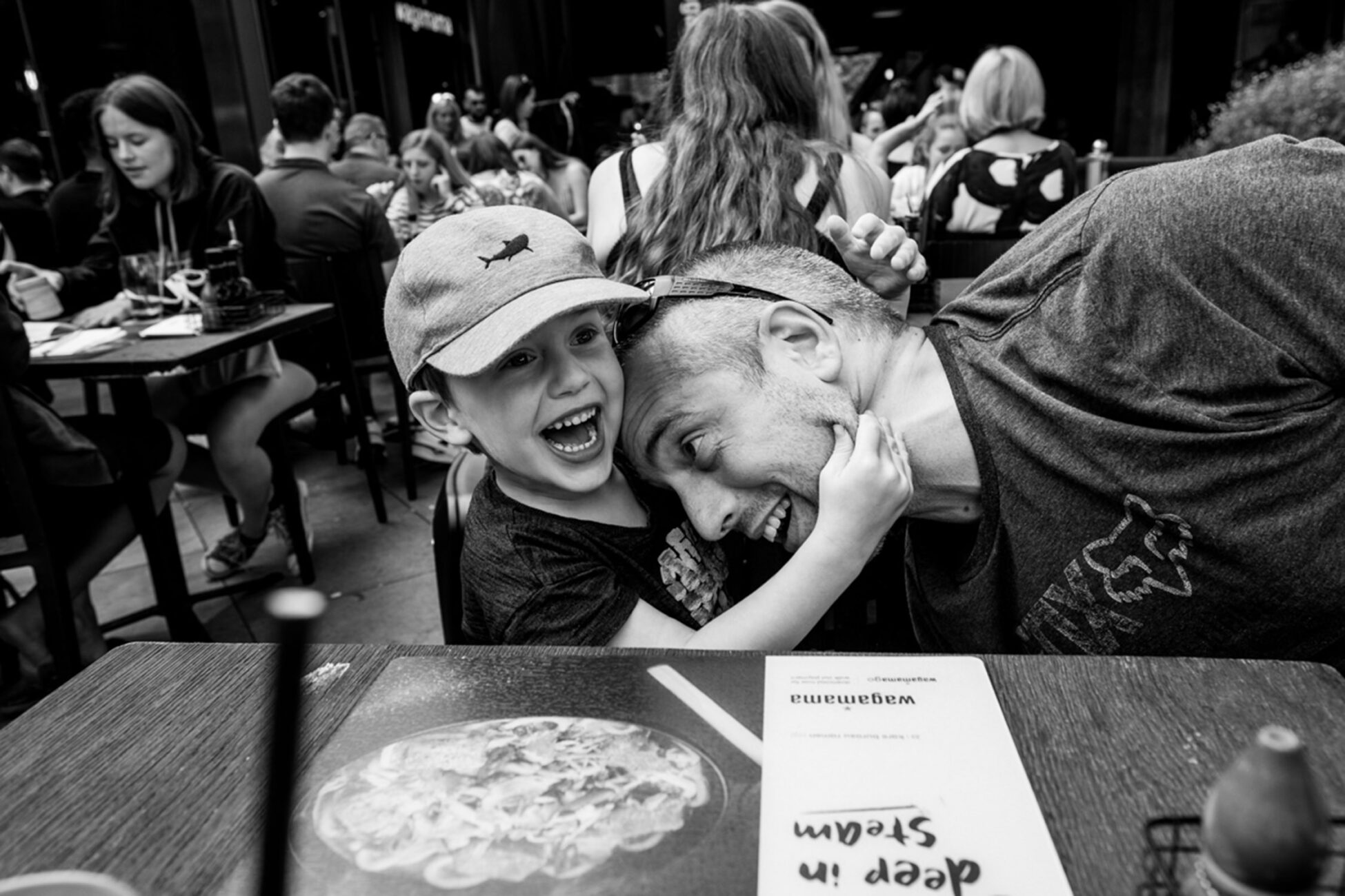 little boy pinches his dad's cheek during a family meal in town.