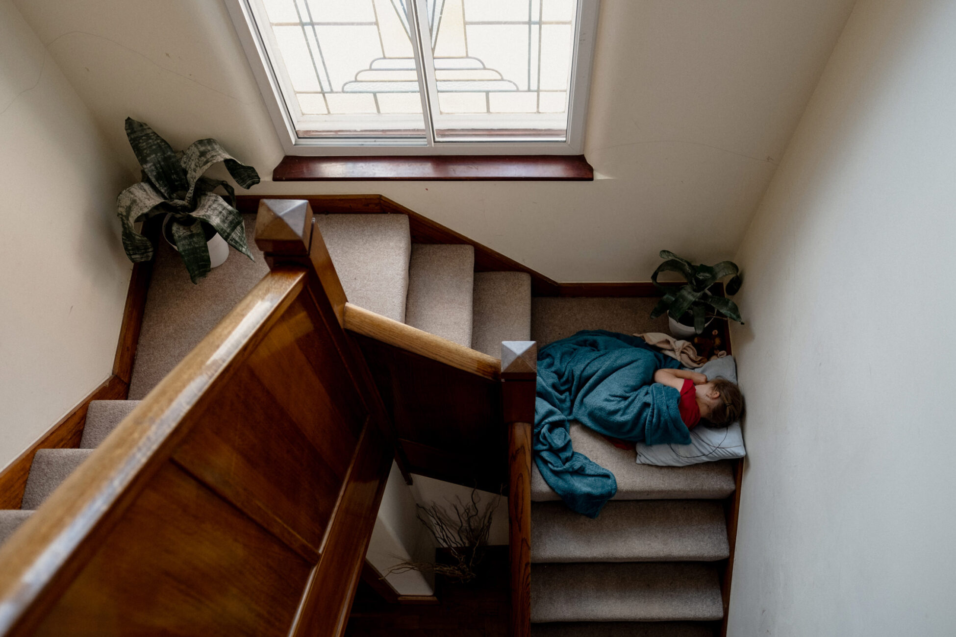 little girl sleeping on the landing of the stairs during a family session in essex