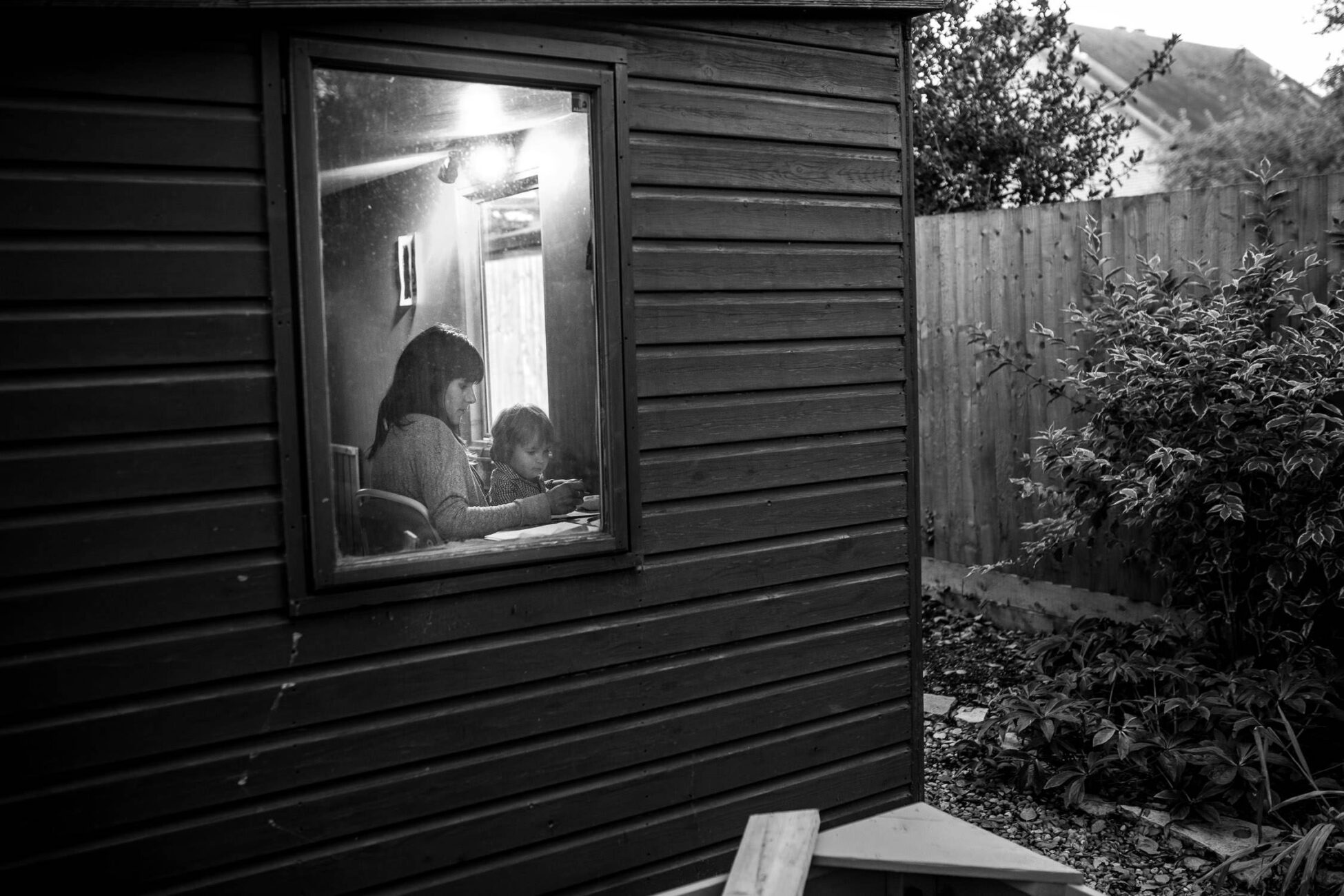 mom and little boy having a quiet moment, drawing and enjoy their garden shed during a family photoshoot