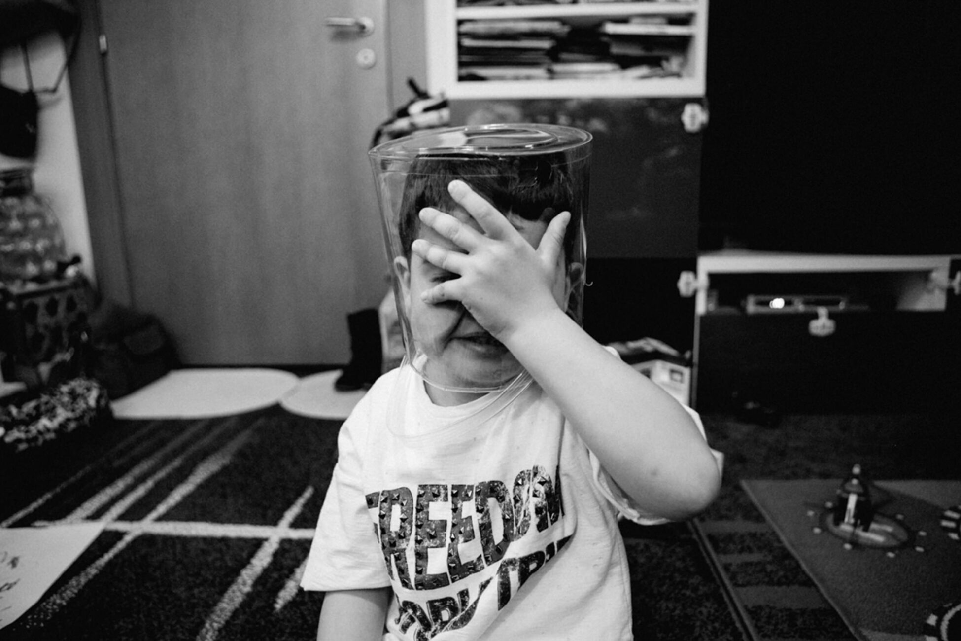 little boywith a plastic container on his head during a family photoshoot